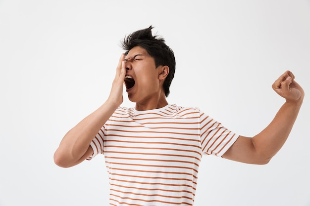 Portrait of sleepy asian man with brown hair in casual t-shirt yawning and covering mouth with fist due to insomnia or fatigue, isolated Premium Photo