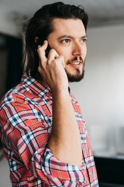 Portrait of a smart young man in plaid shirt talking on cell phone Free Photo