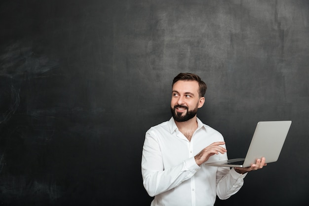 Portrait of smiling adult guy holding silver laptop and looking aside, isolated over dark gray wall Free Photo