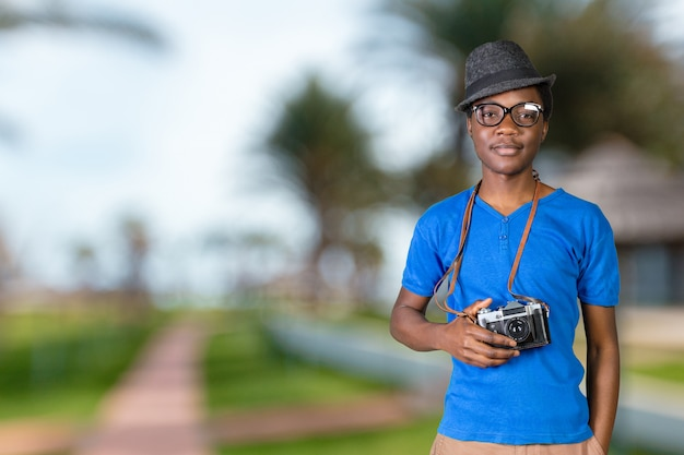 Portrait of a smiling afro american man making photo on retro camera Premium Photo