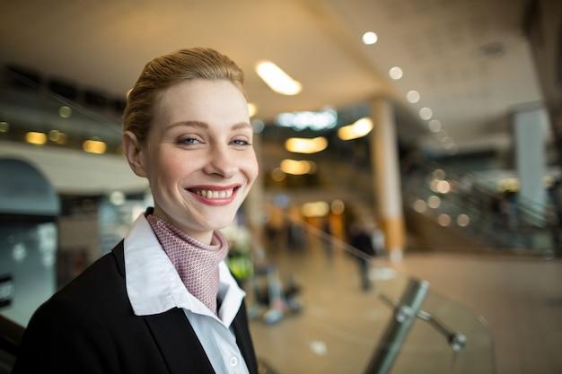 Ritratto di sorridente addetto al check-in della compagnia aerea al banco Foto Gratuite