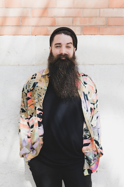 Portrait of a smiling bearded man against brick wall Free Photo