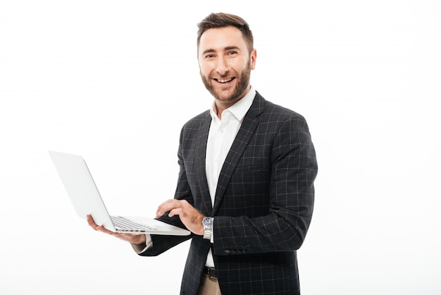 Portrait of a smiling bearded man holding laptop computer Free Photo