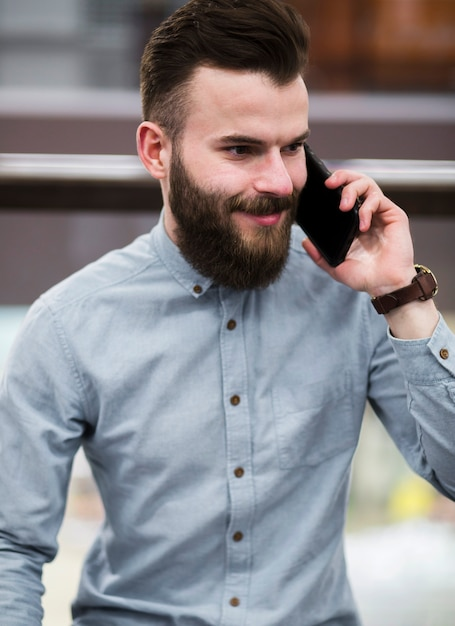 Portrait of a smiling bearded young man talking on mobile phone Free Photo