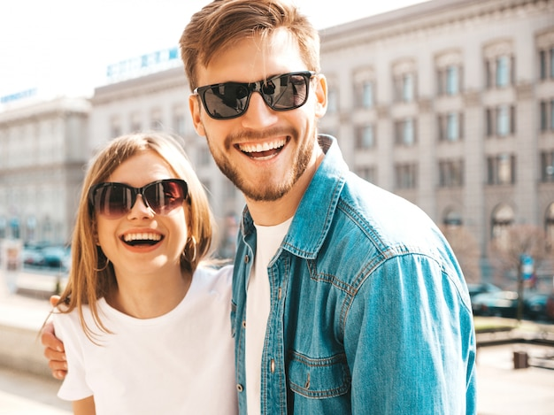 Portrait of smiling beautiful girl and her handsome boyfriend in casual summer clothes and sunglasses.  . hugging Free Photo