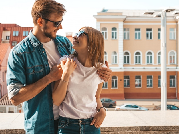 Portrait of smiling beautiful girl and her handsome boyfriend in casual summer clothes and sunglasses. Free Photo