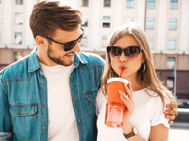 Portrait of smiling beautiful girl and her handsome boyfriend in casual summer clothes.   . with bottle of water and straw Free Photo