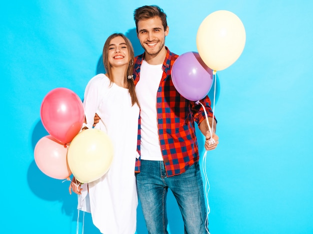 Portrait of smiling beautiful girl and her handsome boyfriend holding bunch of colorful balloons and laughing. happy birthday Free Photo