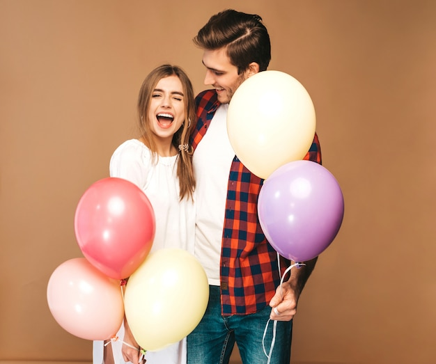 Portrait of smiling beautiful girl and her handsome boyfriend holding bunch of colorful balloons and laughing. happy couple in love. happy birthday Free Photo