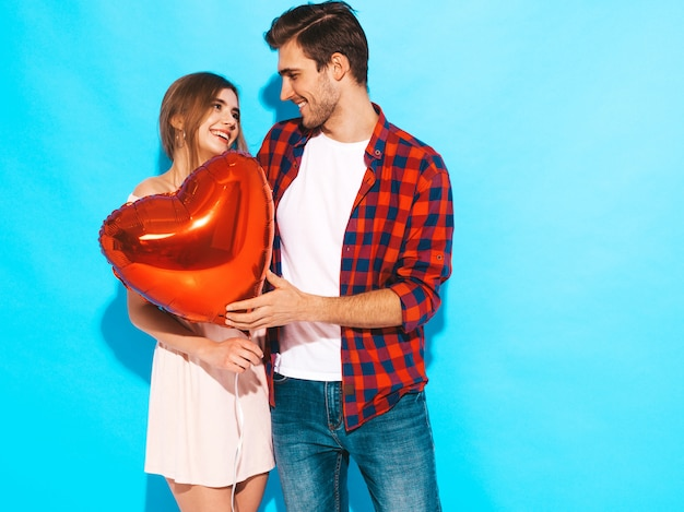 Portrait of smiling beautiful girl and her handsome boyfriend holding heart shaped balloons and laughing. happy couple in love. happy valentine's day. posing Free Photo