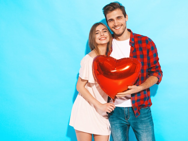 Portrait of smiling beautiful girl and her handsome boyfriend holding heart shaped balloons and laughing. happy couple in love. happy valentine's day. Free Photo