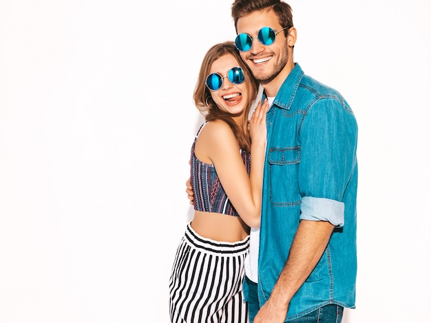 Portrait of smiling beautiful girl and her handsome boyfriend laughing.happy cheerful couple in round sunglasses. Free Photo