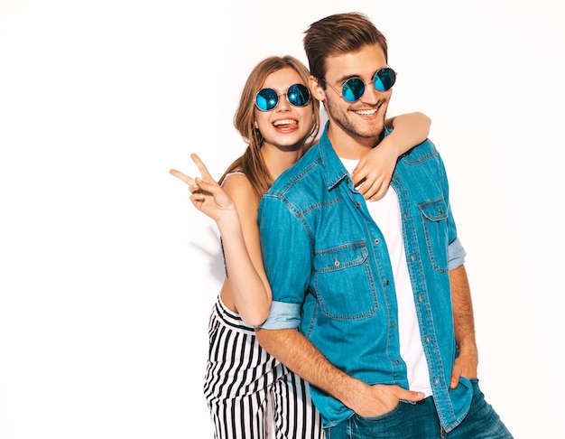 Portrait of smiling beautiful girl and her handsome boyfriend laughing.happy cheerful couple in sunglasses. and showing peace sign Free Photo