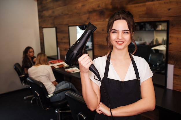 Portrait of smiling beautiful woman hairdresser looking at camera Premium Photo