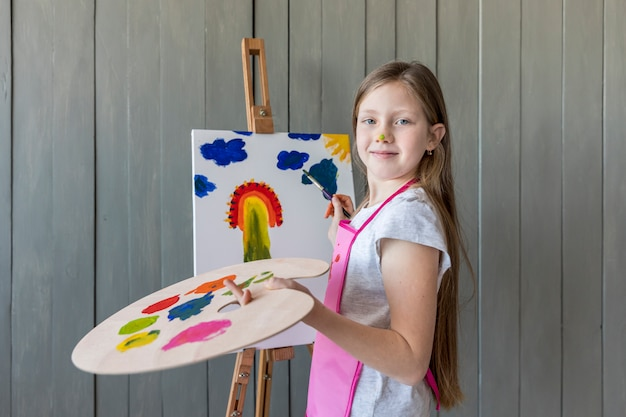 Portrait of a smiling blonde girl holding palette in hand painting on the easel with paint brush Free Photo