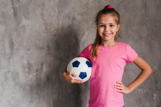 Portrait of a smiling blonde girl with hand on hip holding soccer ball against grey wall Free Photo