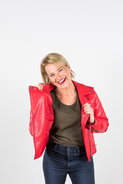 Portrait of smiling blonde mature woman in red jacket standing against white background Free Photo