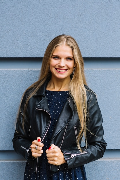 Portrait of a smiling blonde young woman in black jacket standing against wall Free Photo