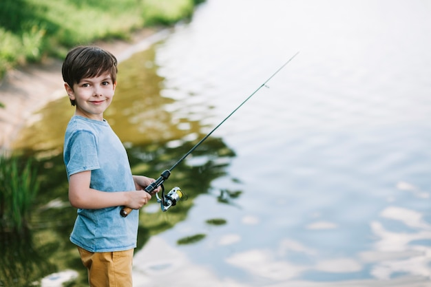 Portrait of a smiling boy fishing on lake Free Photo