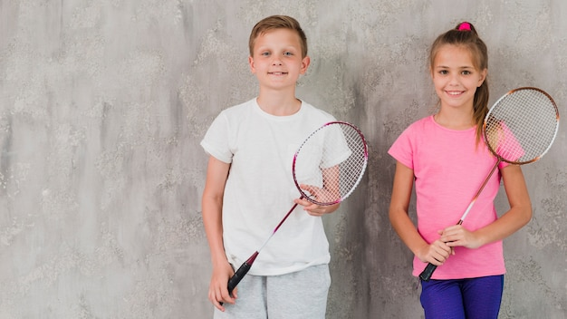 Portrait of a smiling boy and girl holding racket in hands against concrete wall Free Photo