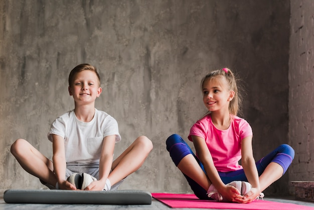 Portrait of a smiling boy and girl sitting together exercising against concrete backdrop Free Photo