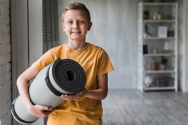Portrait of a smiling boy holding grey rolled up exercise mat in hand Free Photo