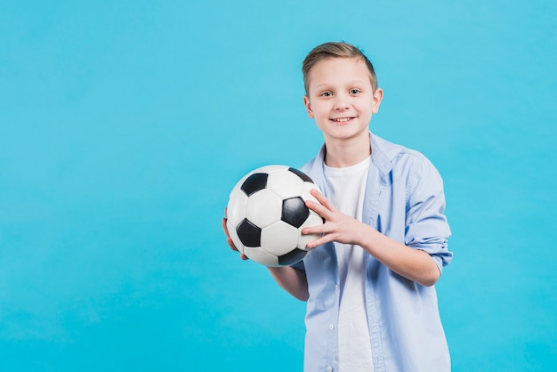 Portrait of a smiling boy holding soccer ball in hand standing against blue sky Free Photo
