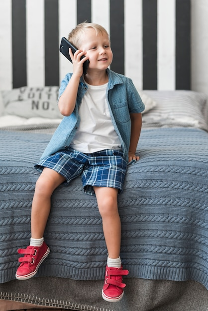 Portrait of a smiling boy sitting on bed talking on smart phone Free Photo