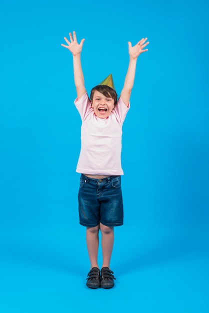 Portrait of smiling boy wearing party hat with arm raised in blue backdrop Free Photo