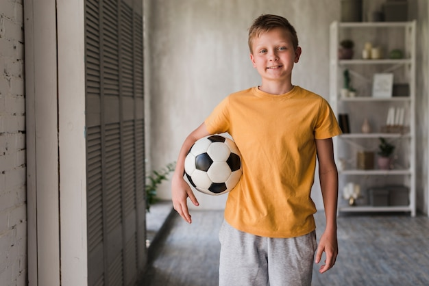 Portrait of a smiling boy with soccer ball Free Photo