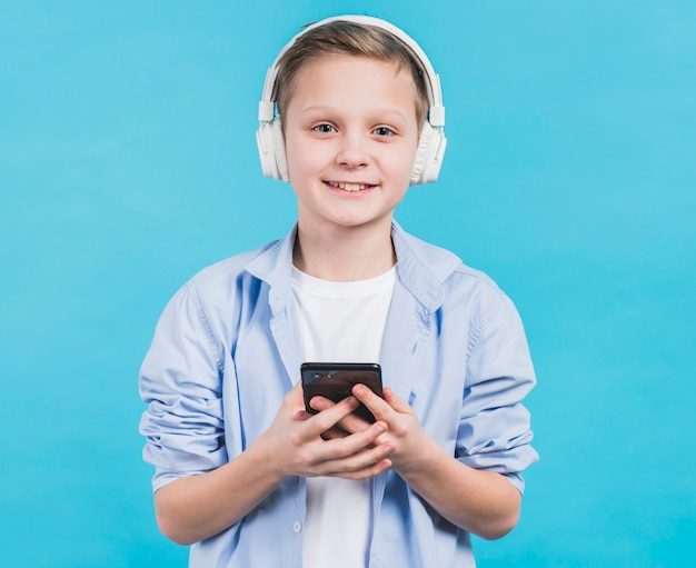Portrait of a smiling boy with white headphone on head holding smartphone in hand against blue background Free Photo