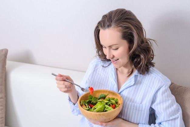 Portrait of smiling brunette eating fresh vegetable, vegetarian salad. Premium Photo