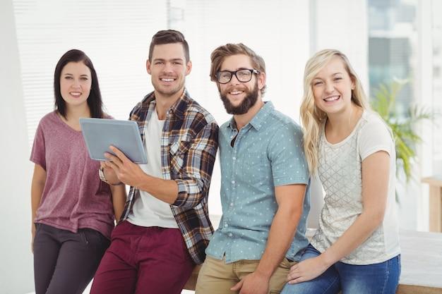 Portrait of smiling business people holding digital tablet Premium Photo