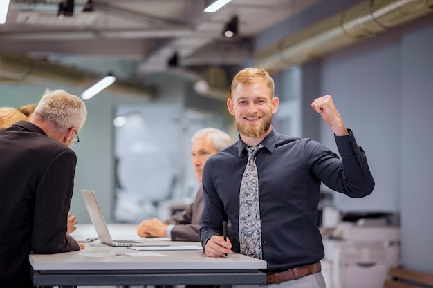 Portrait of smiling businessman clenching his fist while team discussing in the background Free Photo