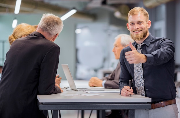 Portrait of smiling businessman showing thumb up sign while team discussing in the background Free Photo