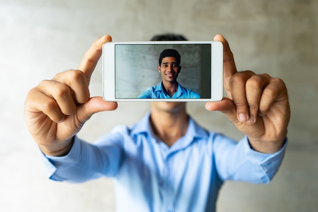 Portrait of smiling businessman taking selfie with smartphone. Free Photo