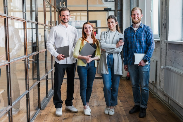 Portrait of smiling businesspeople standing in office Free Photo