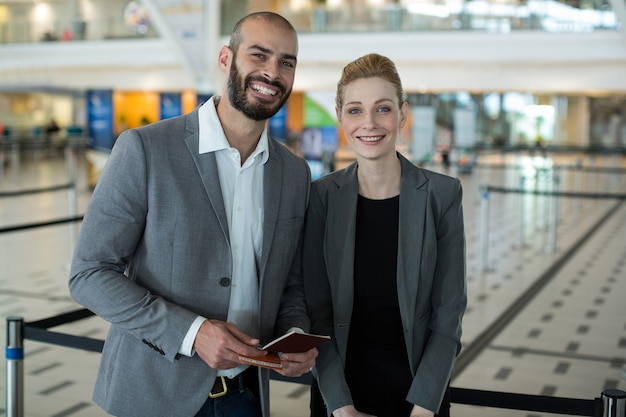 Portrait of smiling businesspeople with passport waiting in queue Free Photo