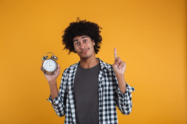 Portrait of a smiling casual african man showing alarm clock Free Photo