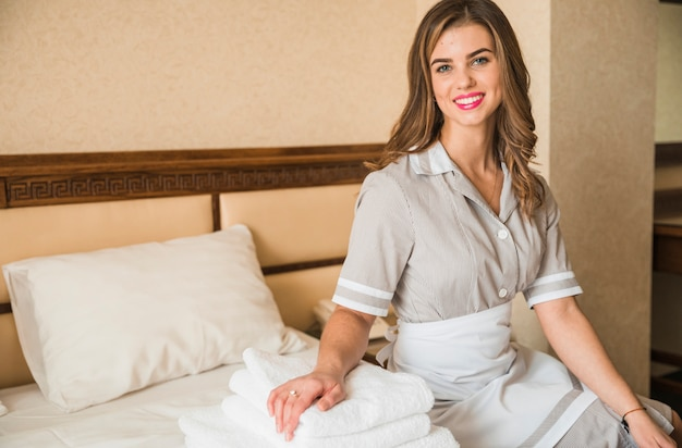 Portrait of a smiling chambermaid sitting on bed with stacked of soft folded towel Free Photo