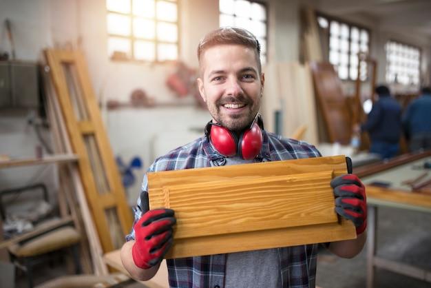 Ritratto di artigiano sorridente che tiene un mobile nel suo laboratorio di falegnameria Foto Gratuite