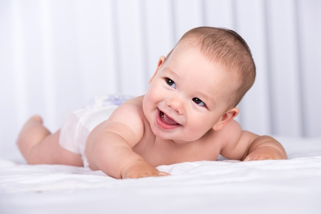 Portrait of a smiling crawling baby on the bed in the room. Premium Photo