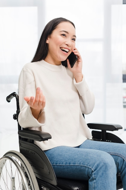 Portrait of a smiling disabled young woman sitting on wheel chair talking on mobile phone shrugging Free Photo