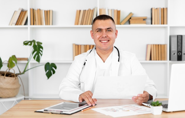 Portrait of smiling doctor sitting on desk Free Photo