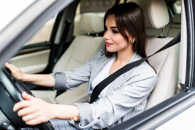 Ritratto di donna sorridente autista allacciare la cintura di sicurezza prima di guidare un'auto. Foto Gratuite