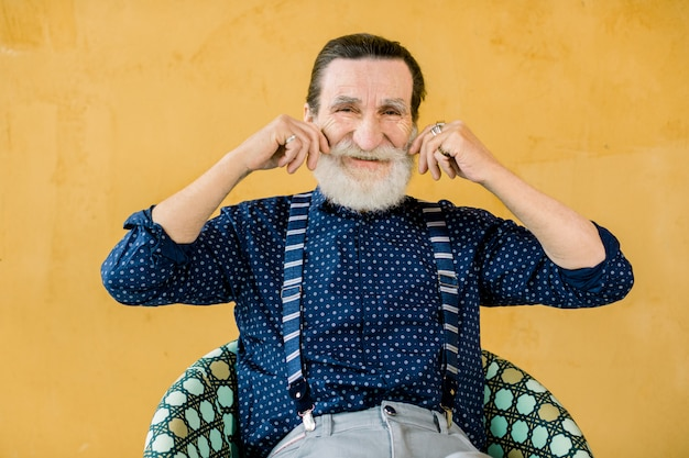 Portrait of smiling elderly bearded man in dark blue shirt and suspenders, posing isolated on yellow studio background, touching his mustache. people emotions and lifestyle concept. Premium Photo