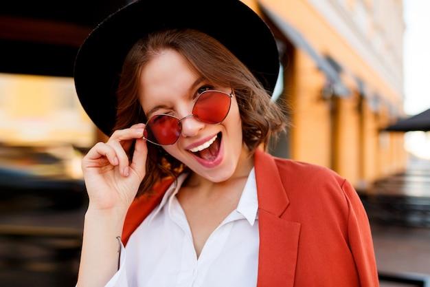 Ritratto di sorridente ragazza europea in simpatici occhiali da sole arancione, giacca e cappello nero. moda autunno. caffè all'aperto. Foto Gratuite