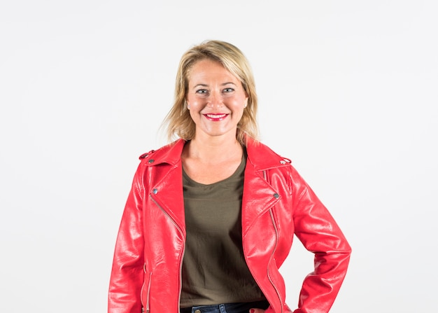 Portrait of a smiling fashionable blonde mature woman in red jacket isolated on white backdrop Free Photo