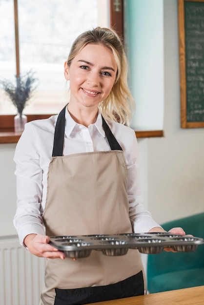 Portrait of a smiling female baker holding baked muffins molds Free Photo