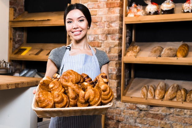 Portrait of a smiling female baker holding basket of baked croissant in bakery shop Free Photo